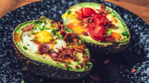 image of an avocado with egg, bacon and hot sauce
